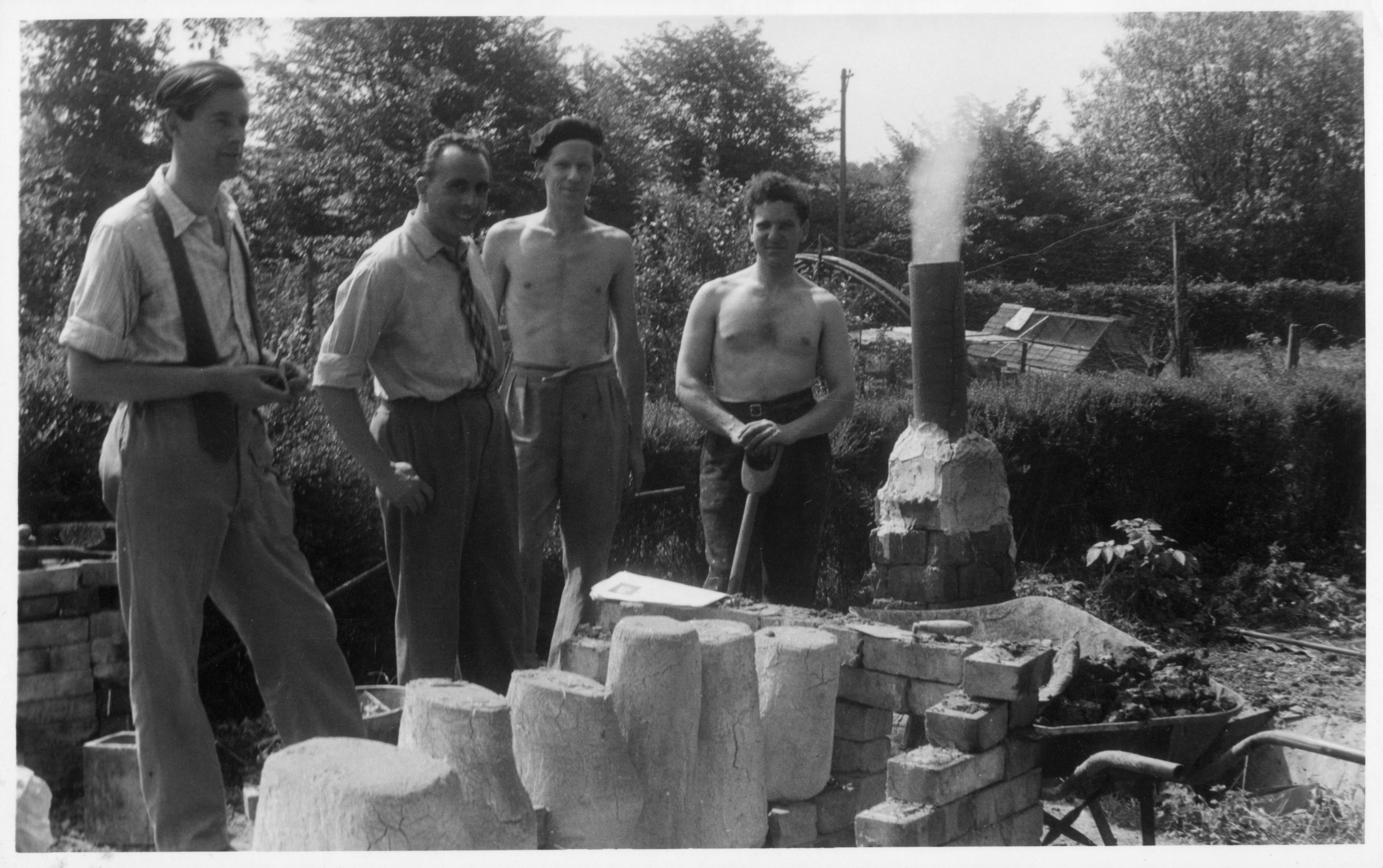 Henry Moore's assistants Oliffe Richmond, Alan Ingham, and Anthony Caro with the homemade Foundry in the garden of Hoglands, c.1950