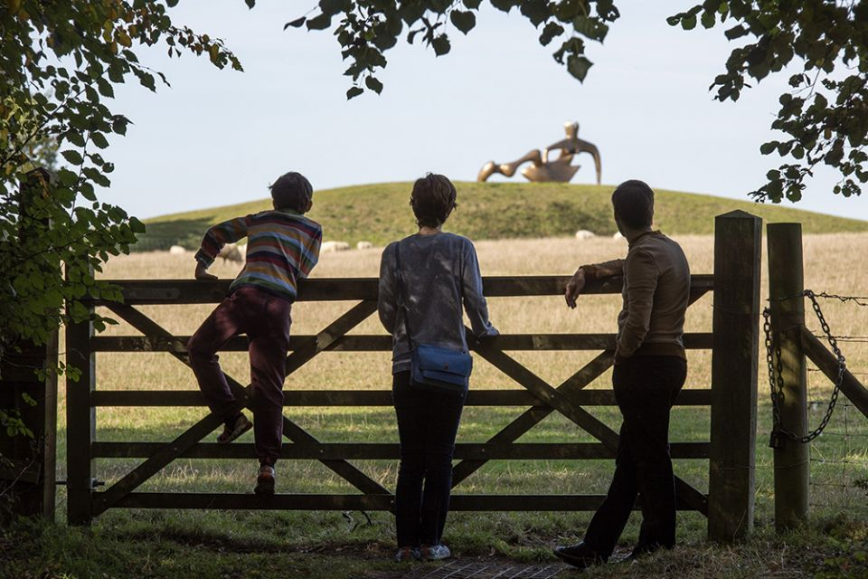 A family leaning on a field gate looking at Henry Moore's 'Large Reclining Figure' in the distance