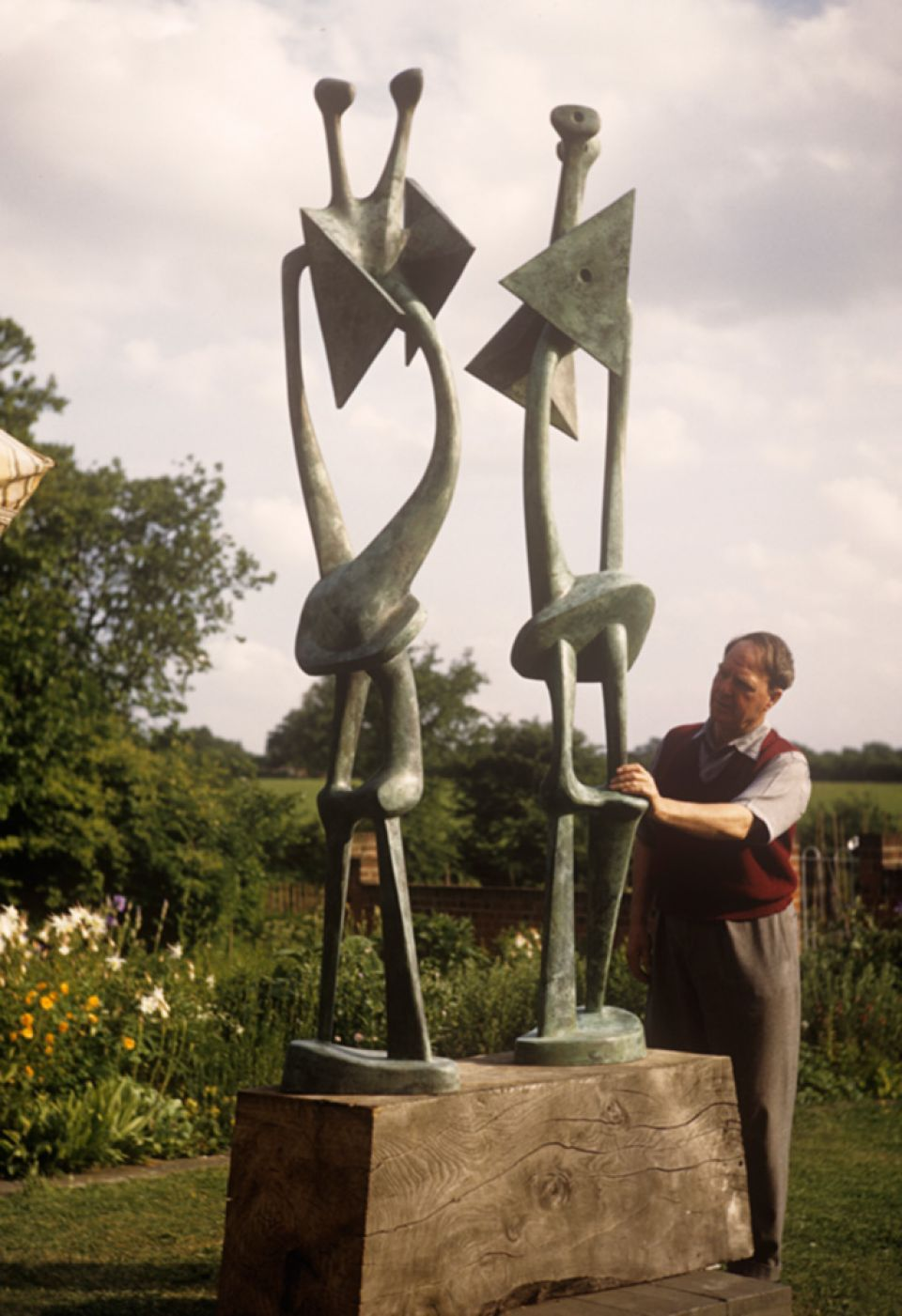 Henry Moore with 'Double Standing Figure' 1950 (LH 291) in his garden in Perry Green, c.1950.