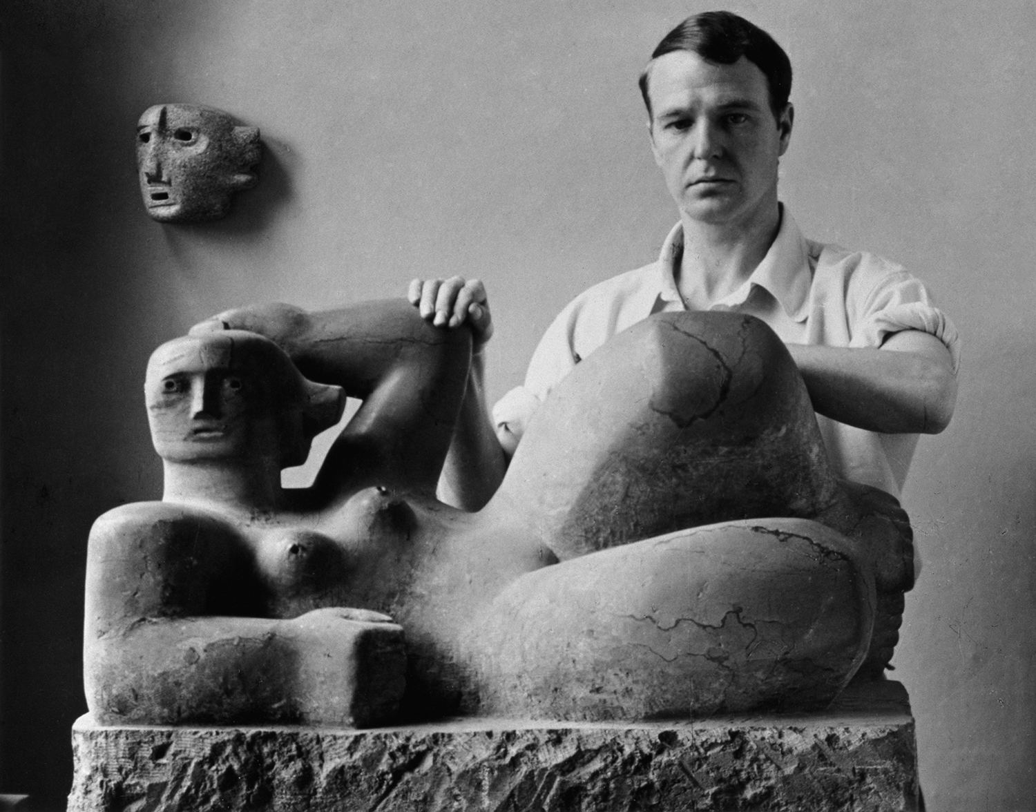 Henry Moore c.1929-30 with Reclining Figure 1929 (LH 59) and Mask 1930 (LH 77)