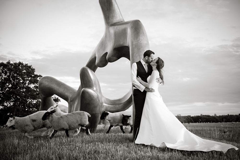 A bride and groom embrace by Henry Moore 'Large Reclining Figure' 1984