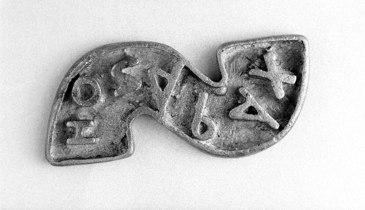 S-shaped copper alloy stamp with relief inscription (c. 300-600 AD)