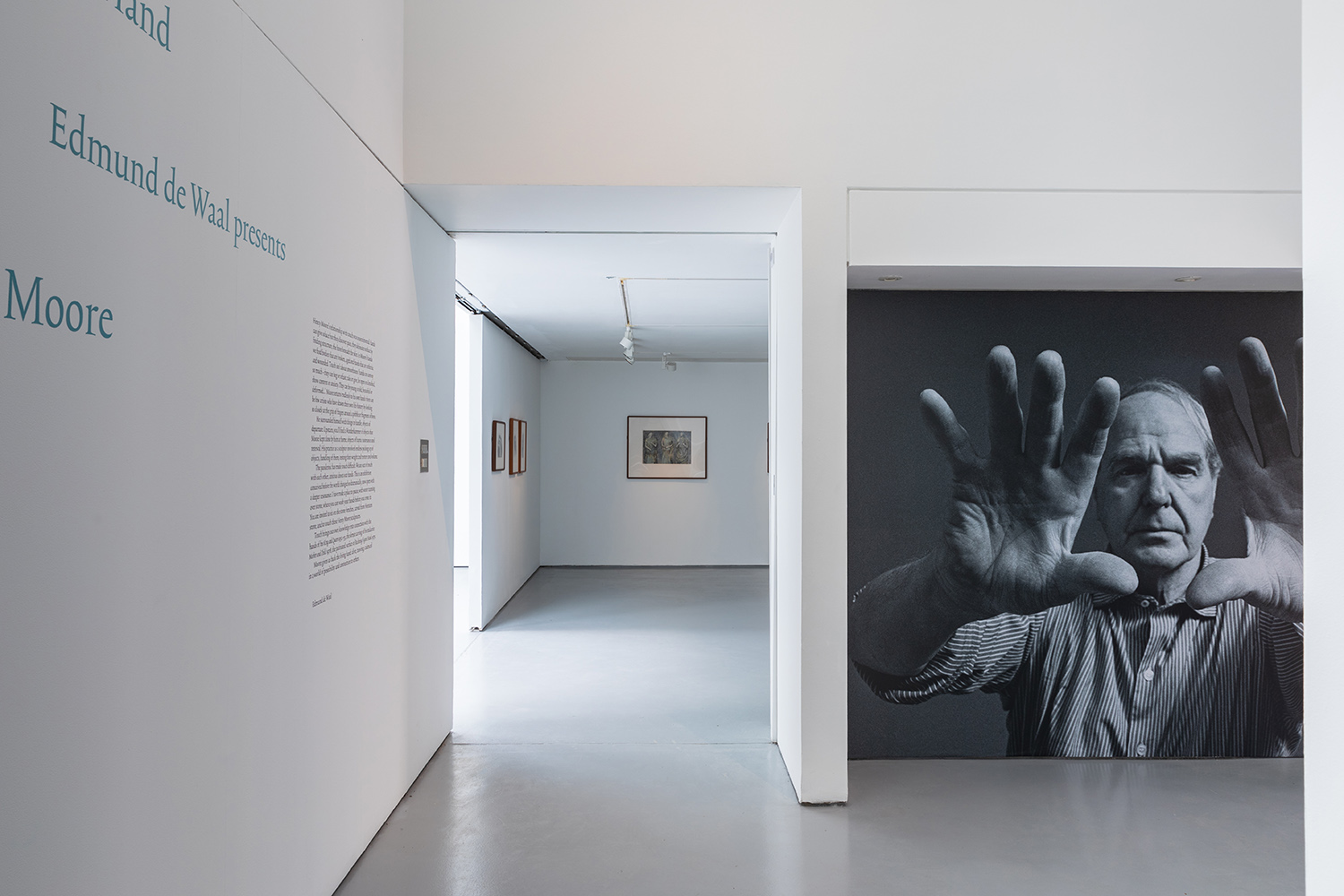 An installation view of the entrance to the 'This Living Hand' gallery, showing a black and white photograph of Henry Moore on one wall and the title text on an adjacent wall.
