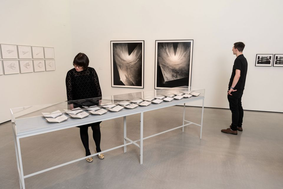 Visitors look at notebooks and photographs by artist Anthony McCall at The Hepworth Wakefield