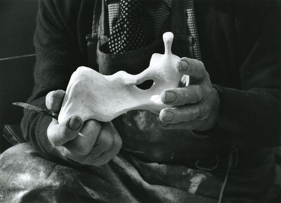 Moore holding the plaster maquette for Reclining Figure: Hand 1976, (LH 707)