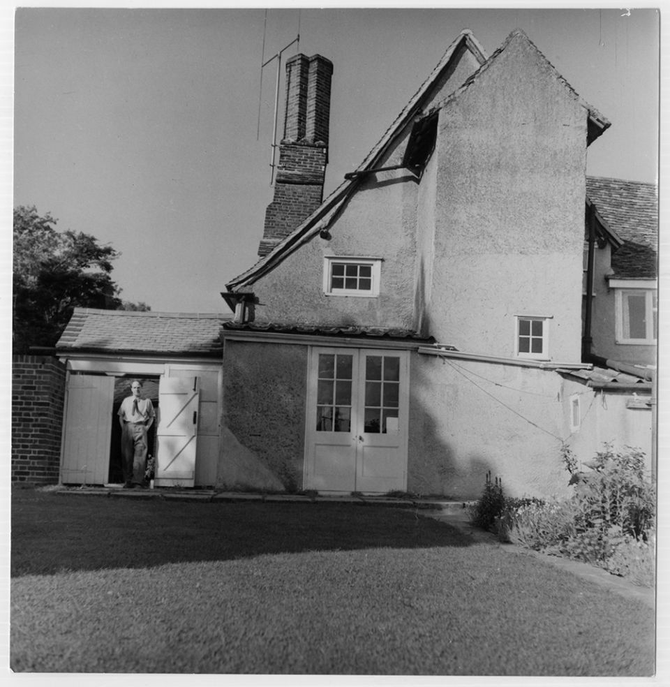 An archive photograph showing sculptor Henry Moore in the rear doorway of his home, Hoglands. Taken around 1940.