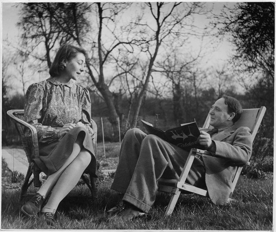 An archive photograph showing Henry and Irina Moore together in the garden of their home. Both are smiling and Moore is reading a book about fellow sculptor Alexander Calder.