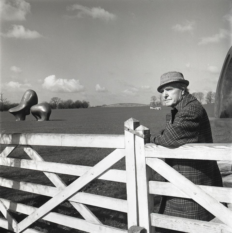Henry Moore in Perry Green with 'Sheep Piece' in the background, 1977