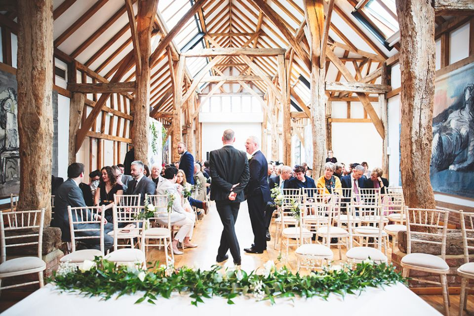 Guests wait for the wedding couple to arrive before a ceremony in the Aisled Barn