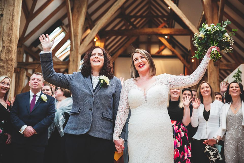 A female couple celebrate the conclusion of their wedding ceremony in the Aisled Barn