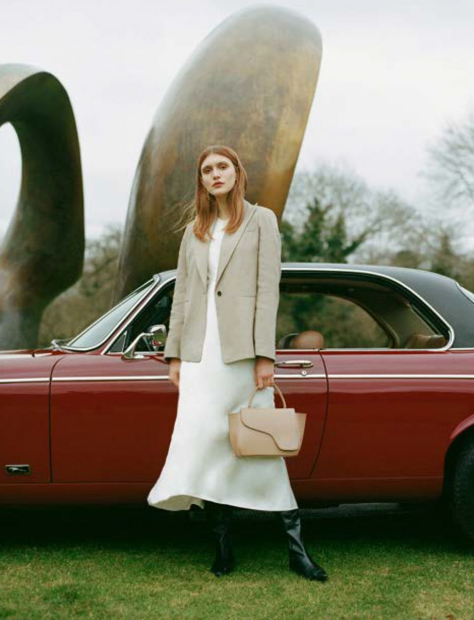 Photo showing a young, female model with a dark red Jaguar car in front of Henry Moore's 'Double Oval' sculpture