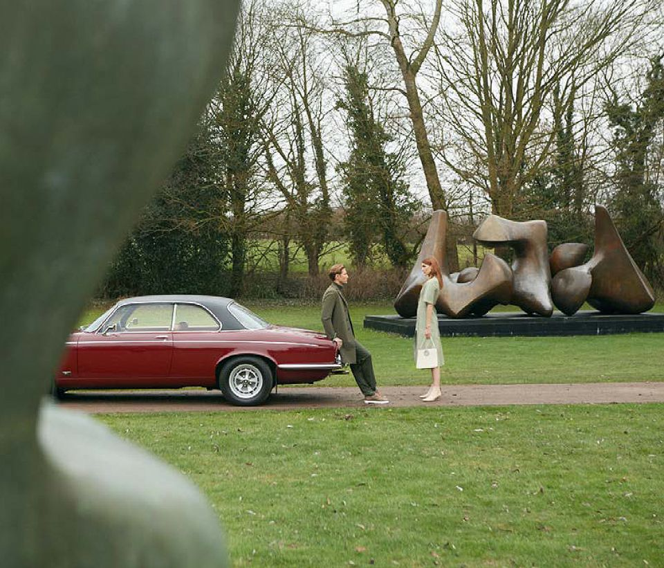 Photograph showing a maroon, 1970s Jaguar car with two models, in front of Henry Moore's sculpure 'Three Piece Reclining Figure: Vertebrae'