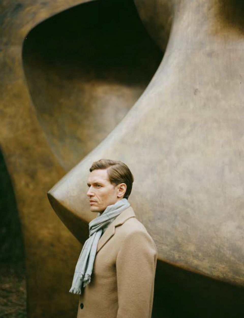 A male model, wearing camel coloured coat and pale blue scarf, in front of the sculpture 'Large Figure in a Shelter'