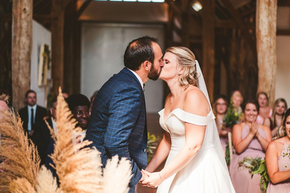 A couple kiss during their wedding ceremony in the Aisled Barn at Henry Moore Studios & Gardens